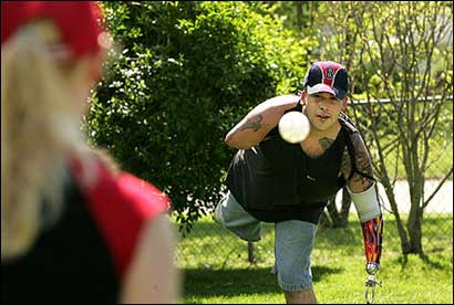 Peter Damon practiced his throws with his wife, Jenn, at his Brockton home June 1, 2005 in preparation for his appearance at Fenway Park.