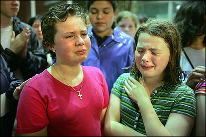 Evelyn Morano (L), 10, and Colleen Curry, 11, shed tears yesterday after learning that their Brighton school was closing.