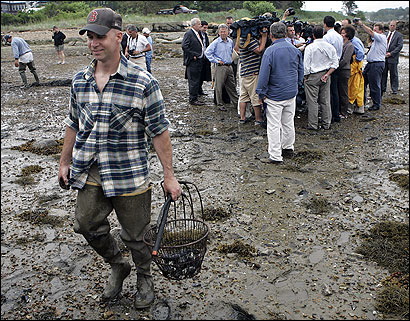 Dennis Nault, a state marine biologist, carried clams dug at the Annisquam River in Gloucester yesterday to test for red tide as Governor Mitt Romney spoke to reporters about aid for those whose livelihoods have been hurt by the algae bloom.