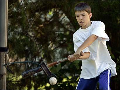 Alex Reimer practices his hitting on a device attached to a basketball pole in his front yard in Natick.