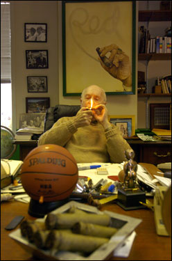 Even in his 80s, Red still loved his cigars. Here, he lights up a stogie in his Washington D.C. office in 2004. The picture behind him depicting the smoke from a cigar spelling 'Red' was made by his brother Zang, who also drew the Celtics' leprechaun logo.