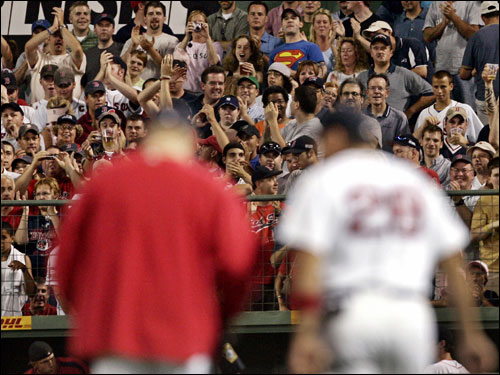 The Fenway crowd stirred to its feet when Curt Schilling (left) and catcher Doug Mirabelli walked from the dugout to the bullpen in the sixth inning last night.