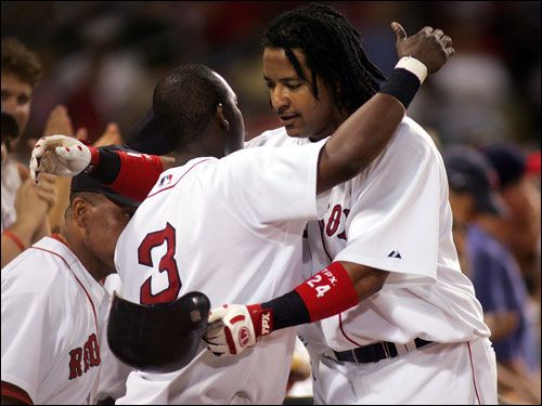 Manny Ramirez gets a hug from Edgar Renteria after hitting a ninth-inning home run last night.
