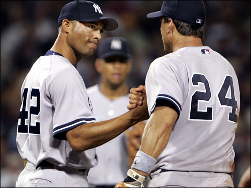 Yankees closer Mariano Rivera (left) gets a hand from first baseman Tino Martinez (right) after getting out of a jam in the ninth inning. Alex Rodriguez is in the background.