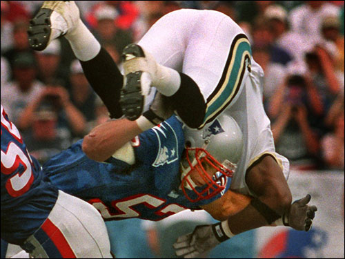 Johnson sent Jacksonville Jaguars running back James Stewart for a loop in this 1996 photo.