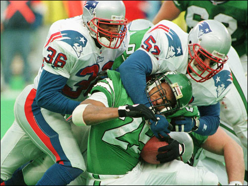 Lawyer Milloy (left) and Johnson tackle the Jets' Adrian Murrell in a November 1996 game.