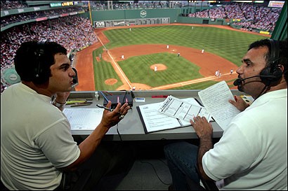 Uri Berenguer (left) and Juan Oscar Baez, at work in Fenway, continue the tradition at the Spanish Beisbol Network.