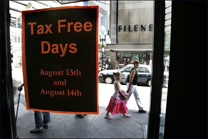A storefront window at Downtown Crossing advertises two days of largely tax-free shopping in Massachusetts. Many merchants will be open from 6 a.m. to midnight today and tomorrow.