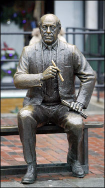 The statue of Red Auerbach still sits atop a bench in Boston's Faneuil Hall Marketplace. The statue shows typical Red, with a cigar in one hand and a rolled-up program in the other.