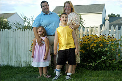 Philip Antonelli Jr., 8, with father Philip, mother Lisa, and sister Molly, 5, at their Dracut house. The youth's delivery led to brain damage.