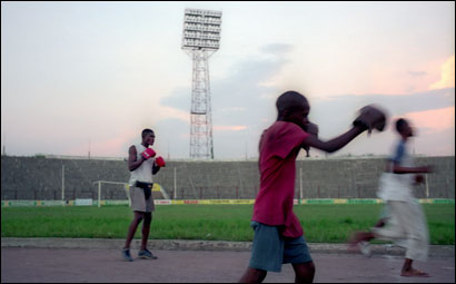 The decaying stadium where Muhammad Ali fought George Foreman in 1974, the fight was known as 'Rumble in the Jungle'. A young Congolese fighters training along the dirt track in the stadium, in Kinshasa, Democratic Republic of Congo.