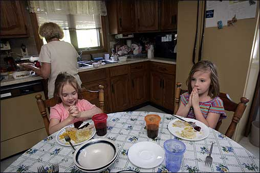 Sisters Alexis O'Neal (left), 6, and Jessica O'Neal, 7, remembered to say grace in the middle of dinner at their great-grandmother's house (rear) in Taunton.
