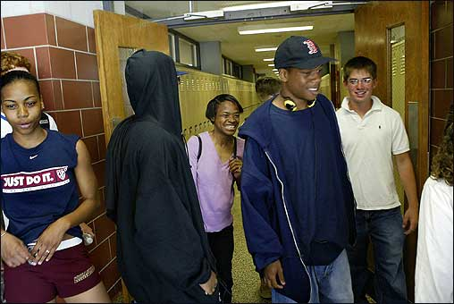 Meisha Jackson (left) and Chris Bird (in background, at right) served as guides Tuesday, providing a tour of Bourne High School for Tevin Verrett (with hood), Terrez Verrett (Red Sox hat), and their mother, Terrial Wooten. Eight Louisiana teenagers staying at Otis Air National Guard Base toured the high school Tuesday.