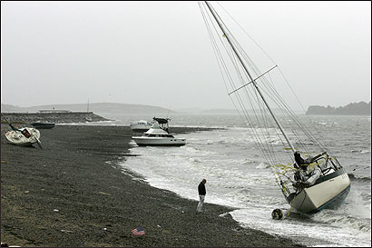Carl Foster of South Boston checked the condition of a sail boat that was ripped off its moorings and pushed onto the rocks next to the South Boston Yacht Club.