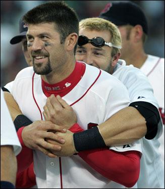 Jason Varitek (left) got a bear hug from behind from teammate Kevin Millar.