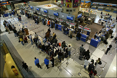 Passengers waited in line yesterday by the United Airlines counter at Logan International Airport.