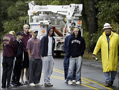 A Verizon employee walked past Algonquin Regional High School students yesterday at the scene of the fatal crash in Southborough.