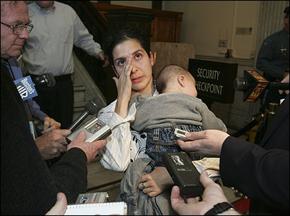 Rose Gonzalez, with son Marcos, 5 months, of Somerville, spoke after urging Governor Mitt Romney to return the Guard.