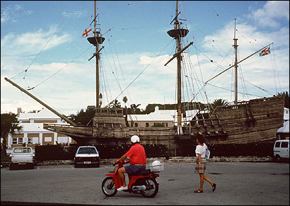 People pass by the 'Deliverance,' a full-size model of the ship the castaways built to take them on to Virginia, in Bermuda.