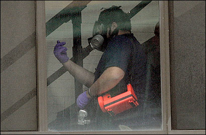 An investigator donned protective gear yesterday in the building where police said they found a methamphetamine laboratory.