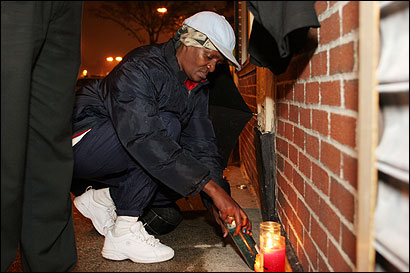 Linda Wyne of Mattapan paused near a makeshift shrine for Brandon Patterson on the corner of Evelyn Street and Blue Hill Avenue. He was fatally shot outside a popular Jamaican restaurant in Mattapan.
