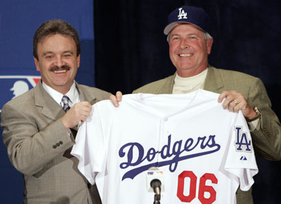 Los Angeles Dodgers general manager Ned Colletti, left, presents new team manager Grady Little with his team jersey and ball cap at a news conference at the winter baseball meetings, Tuesday, Dec. 6, 2005, in Dallas. (AP Photo/Tony Gutierrez)