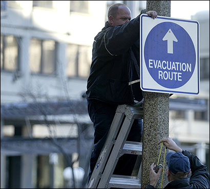 Transportation Department workers installed an emergency evacuation route sign on Cambridge Street yesterday.