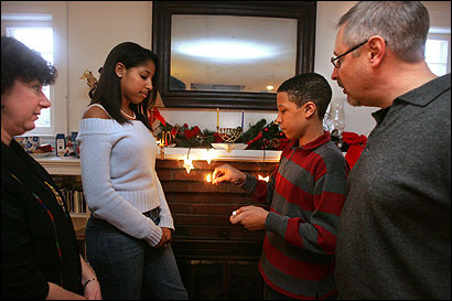Tasha (from left), Mia, Leo, and David Balsom lit the menorah at their Lexington home. They also celebrate Christmas and Kwanzaa.