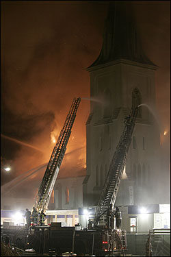 A fire tore through First Baptist Church in Jamaica Plain on Jan. 18, severely damaging the pre-Civil War landmark, and destroying a treasured pipe organ that was spared in an earlier blaze almost 30 years ago. At left, Boston Fire Department Lieutenant William McCarthy walked down an aisle of the ice-coated ruins of the First Baptist Church. &nbsp; <img src ='http://cache.boston.com/bonzai-fba/File-Based_Image_Resource/dingbat_arrow_icon.gif' alt='' title='' height='9' width='4' border='0' /> <a target='new' href ='http://www.boston.com/news/local/massachusetts/articles/2005/01/19/blaze_destroys_historic_church'>Story