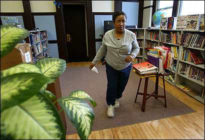 Joy Oliver, principal of the Henry L. Higginson Elementary School, tidied up the Roxbury school's library last month. Black principals now make up nearly half of the 148 principals.