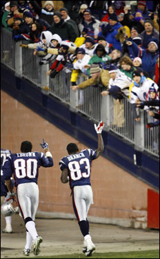 Wide receiver duo Troy Brown (left) and Deion Branch (right) salute the crowd after the game.