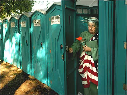 Woman dressed as Statue of Liberty emerging from portable toilet
