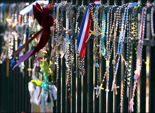 Rosary beads, ribbons, and notes along the wrought iron railing that surrounds the gravesite.