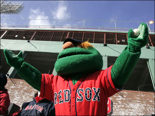 Wally the Green Monster, mascot of the Red Sox, leads the cheers as the truck containing equipment for spring training left for Florida today.