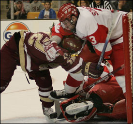 In a gripping Beanpot final, BU's Kevin Schaeffer and goalie John Curry keep BC's Chris Collins (left) under wraps.