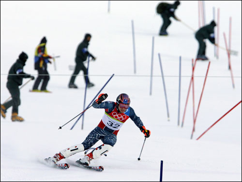 The gates would be his downfall...Bode Miller came down the hill on the run in which he would be disqualified. The workers behind him were smoothing out the course for the next racer.