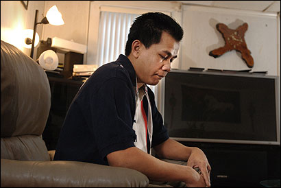 Tai Kim of Lowell sat before the TV he bought before learning that investments he made were lost in an alleged pyramid scheme targeting Cambodians.