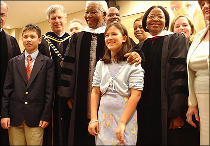 Nelson Mandela and his wife Graca Michel are joined by a 12-member University of Massachusetts delegation after a ceremony in the university gave honorary degrees to Mandela and Michel. Behind Mandela's right shoulder is University President Jack M. Wilson.