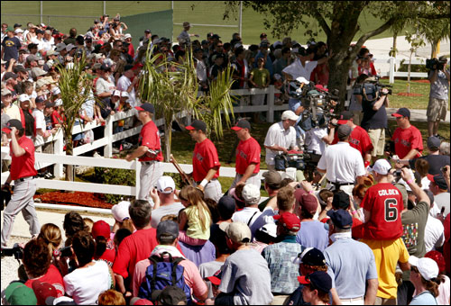 Red Sox players head out to the fields for Thursday's first official team workouts under the gaze of the media and fans in Fort Myers.