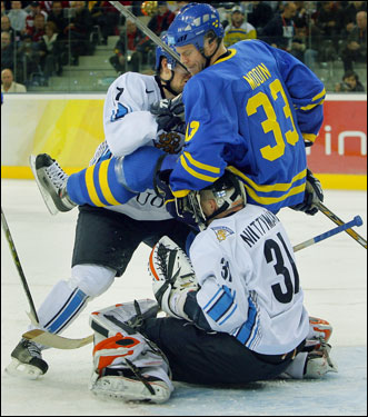 Sweden's Fredrik Modin took a seat on top of Finland goalie Antero Niittymaki, courtesy of a shove from Finalnd's Antti-Jussi Niemi.