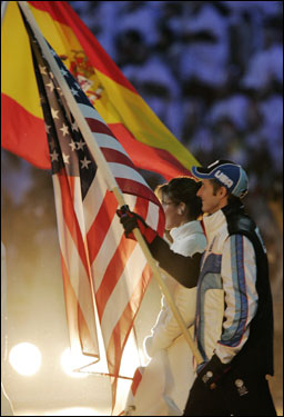 Speed skater Joey Cheek carries the American flag as he leads the US delegation during the closing ceremonies.