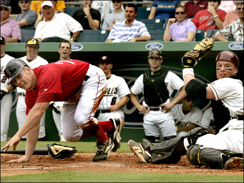 Red Sox minor leaguer Brandon Moss, at left, slides home safely as BC catcher Shawn McGill, couldn't handle the throw home.