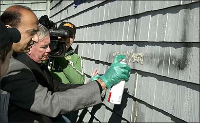 Saeed Shahzad, M.D., of the Islamic Center of New England, left, and Rev. John E. Kelly of St. James Church in Stoughton lend a hand to clean symbols of hate left on the outside of the Striar Jewish Community Center in Stoughton.
