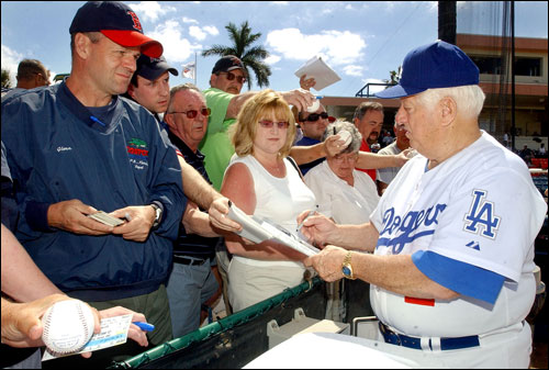 Tommy Lasorda signed autographs for fans before the start of the game.