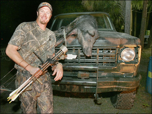 Timlin, sporting his trademark fatigues, posed with the wild feral hog. Wild feral hogs were imported from Spain in the 1520s. They were released or escaped into the wild at Port Charlotte, Fla., possibly by Ponce de Leon, who was seeking the fountain of youth.