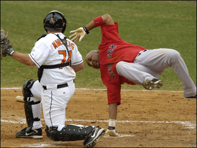 Enrique Wilson gets flipped in a failed attempt to score on Baltimore's Brandon Marsters.