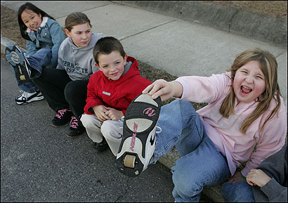 From left: Thuy Nguyen, Darby McLaughlin, Cole Ryan, and Devin Connolly show off their Heelys. Many schools ban skating in the shoes.