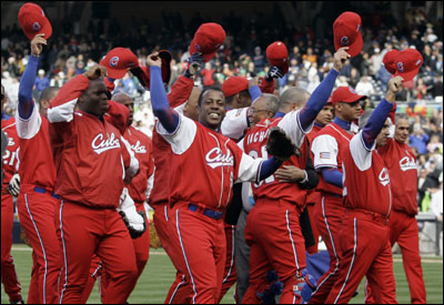 Members of the Cuban team raise their caps in celebration after defeating the Dominican Republic 3-1. They take on Japan in the WBC final.
