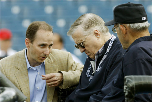 Yankees general manager Brian Cashman (left) talked with owner George Steinbrenner (center) and Yogi Berra (right) before the game.