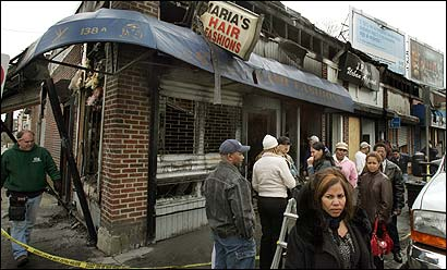 Maria Joseph (lower right) stands outside her Maria's Hair Fashions, which was heavily damaged yesterday by an early-morning blaze that spread rapidly.